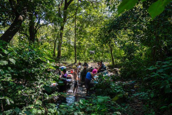 La embotelladora de Coca-Cola sobreexplota el acuífero de Nejapa afectando al abastecimiento de las comunidades próximas. Los vecinos deben acudir a los ríos y quebradas para asearse y lavar sus enseres y ropas.  Para producir un litro de Coca-Cola son necesarios 2,5 litros de agua. (Quetzaltepeque, Nejapa, El Salvador).  ©Calamar2/ Pedro ARMESTRE