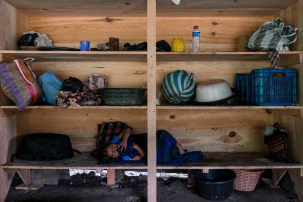 """Una niña descansa en una estantería del campamento de resistencia instalado contra la hidroeléctrica española Ecoener. Las mujeres y los niños vigilan durante el día. Por la noche toman el relevo los hombres más jóvenes. El río Cambalam, donde la hidroeléctrica española pretende instalarse, cruza la selva guatemalteca con varias cascadas y es sagrado para las poblaciones mayas. """"La fuerza y la naturaleza del jaguar y el tigre bañado en oro"""", significa Cambalam en el dialecto kanjobal. Los vecinos que se oponen al proyecto mantienen desde 2011 un campamento las 24 horas para evitar el paso de las máquinas de la empresa. © Calamar2/Pedro ARMESTRE"""