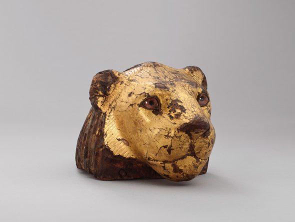 Elemento de un mueble en forma de cabeza de león.