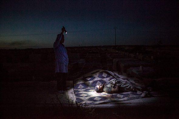 Un rebelde sirio ilumina el cadáver de un combatiente rebelde durante su entierro en Alepo, Siria, 2012. Foto: Manu Brabo.