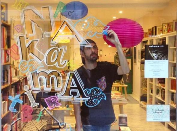 El artista Borja Robles decora el escaparate de la librería Nakama en Madrid.