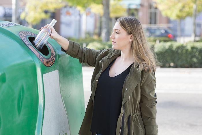 Una mujer recicla una botella de Vidrio.