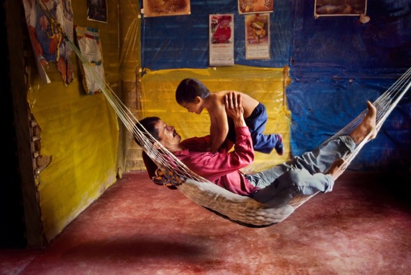 Un padre y su hijo juegan en una hamaca en su casa. La Esperanza. Colombia. 2004.