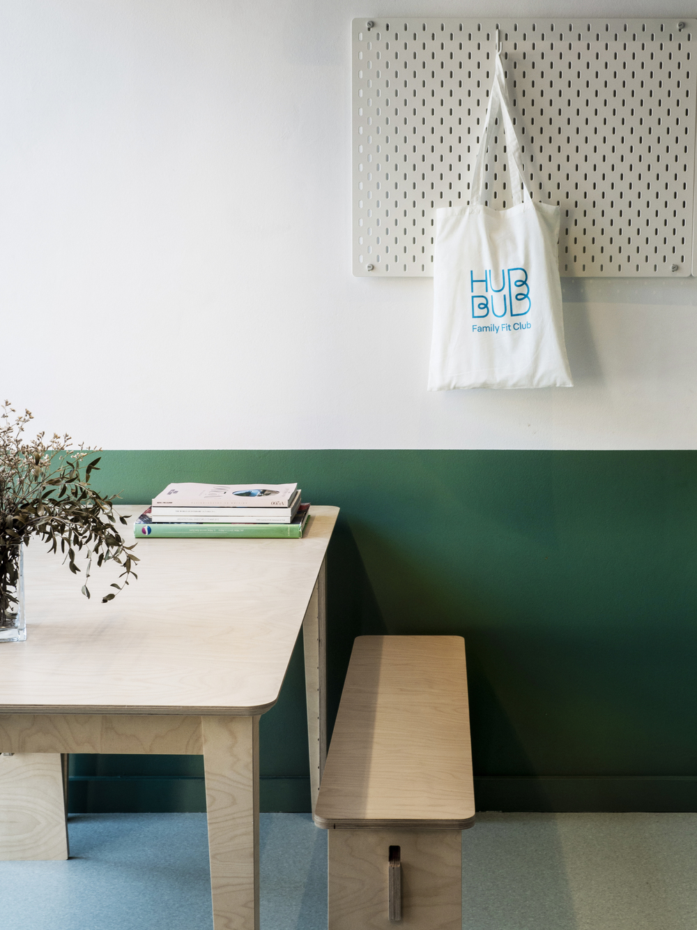 pared verde y mesa y banco de madera. Hubbub Family Fit Club.