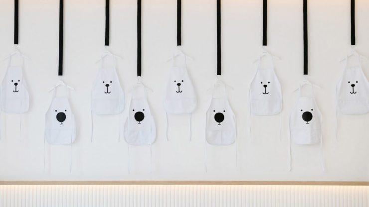 Restaurante para niños White and The bear. Dubai. Interiorismo minimalista. Delantales osito