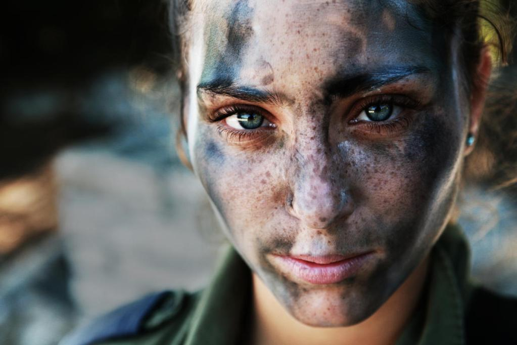 An 18 year old IDF soldier pauses after a long run in full gear and battle paint. By Asher Svidensky