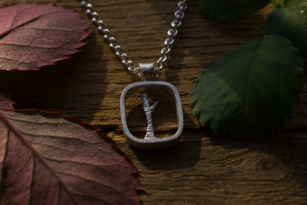 Silver tree pendant on wood with rose leaves
