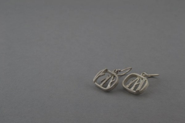 Silver tree earrings laid flat