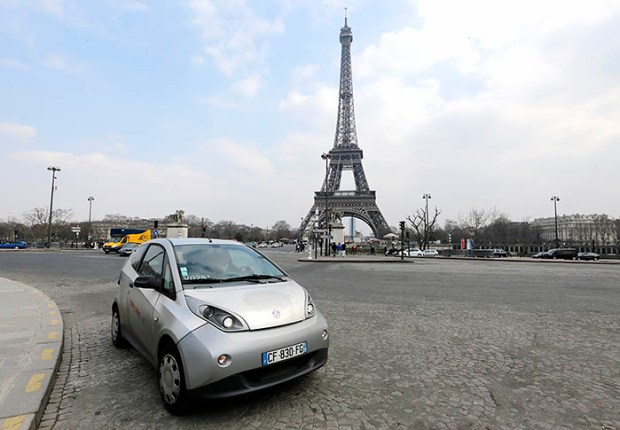 A Paris Autolib' electric car is seen next to the Eiffel tower in Paris