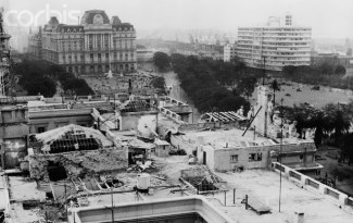 22 Jun 1955, Buenos Aires, Argentina --- Where Rebel Bombs Blasted Buenos Aires. Buenos Aires, Argentina: A bomb-damaged area in Buenos Aires. Rebel boms aimed at government buildings fell here during last week's one-day revolt of navy and air force officers. Government House was one of the official buildings struck. The presidential reception room was destroyed, but President Juan Peron was not in the building. Roof of Government House is in foreground; the Ministry of Marine Building at right and the post office at left. --- Image by © Bettmann/CORBIS