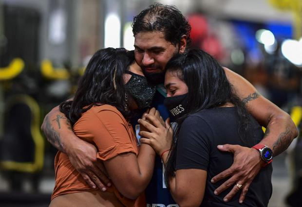 Raúl Gutiérrez abraza a sus hijas en su gimnasio en Lanús, provincia de Buenos Aires, Argentina, el 21 de abril de 2021. (Foto de RONALDO SCHEMIDT / AFP).