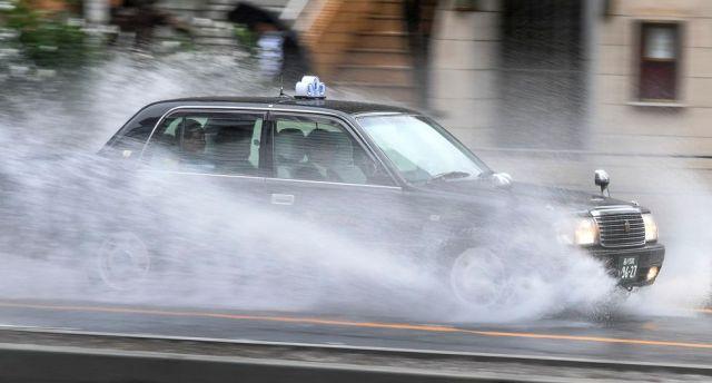 Un taxi que transportaba pasajeros acelera por el agua cubriendo una carretera en el distrito de Aoyama. (Foto: AFP).