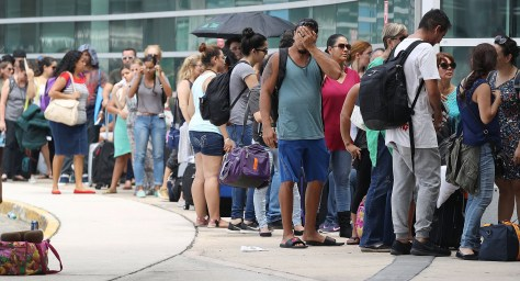 SAN JUAN, PUERTO RICO - SEPTEMBER 26: People wait in line to get a flight out of the Luis Munoz Marin International Airport as they try to return home or escape the conditions after Hurricane Maria on September 26, 2017 in San Juan, Puerto Rico. Some of the people have waited days at the airport in hopes of getting onto a plane after Hurricane Maria, a category 4 hurricane, devastated the island. (Photo by Joe Raedle/Getty Images)