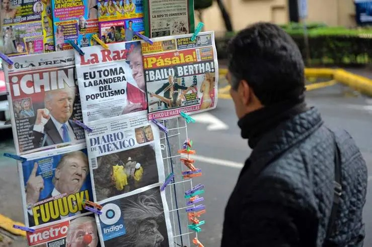 Mexican look at newspapers with their headlines referring to the eventual triumph of Donald Trump on November 9, 2016 in Mexico City. / AFP / PEDRO PARDO