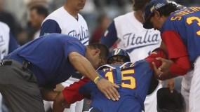 El cátcher de Venezuela, Salvador PéSalvador Pérez es ayudado a levantarse cuando se lesionó.