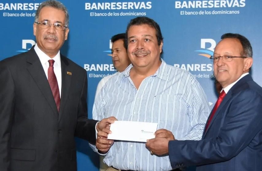 Simón Lizardo y el ministro de Agricultura, Ángel Estévez, entregan cheque a    Manuel      Mirabal.