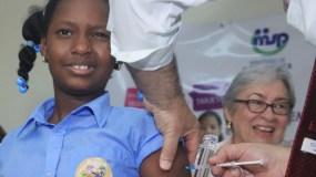 Esta pequeña hace un gesto de molestia   mientras le aplican la primera dosis de la vacuna.