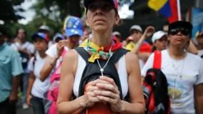 Una mujer sostiene un rosario alrededor de su cuello durante una marcha silenciosa a la Conferencia Episcopal venezolana en homenaje a las al menos 20 personas muertas en disturbios.