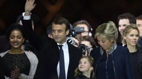 El presidente electo francés Emmanuel Macron, su esposa Brigitte Trogneux  y su hija Tiphaine Auziere  saludan a los partidarios frente a la pirámide en el Museo del Louvre en París, después de la segunda ronda de las Elecciones presidenciales francesas.  AFP