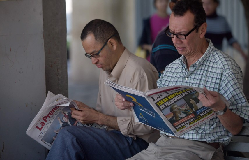 Men read newspapers a day after general election in Honduras, in Tegucigalpa on November 27, 2017. Initial election results released early Monday in Honduras showed opposition candidate Salvador Nasralla leading President Juan Orlando Hernandez, after a tense evening that saw both men declare themselves the winner before official numbers were announced. / AFP / Rodrigo ARANGUA