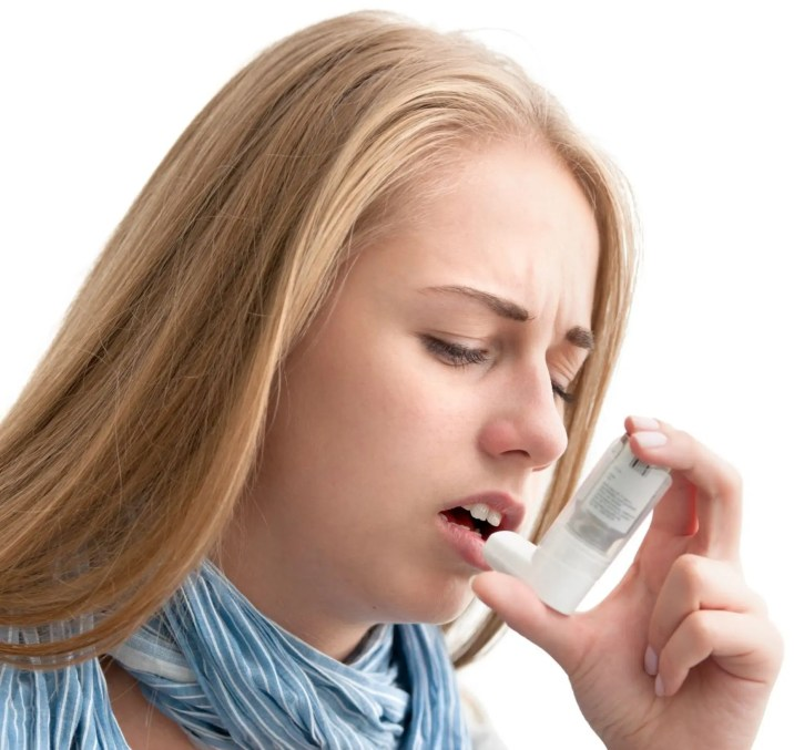 21817831 - young woman using an asthma inhaler as prevention