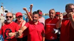 Activistas defensores de los inmigrantes dan la bienvenida al guardacosta Diciotti, con 67 migrantes a bordo, en el puerto de de Trapani, en Sicilia.