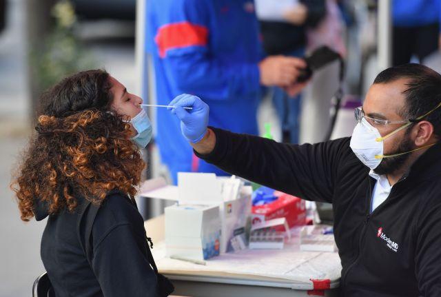 Un sanitario toma una muestra nasal pra el examen PCR a una estudiante en Nueva York.