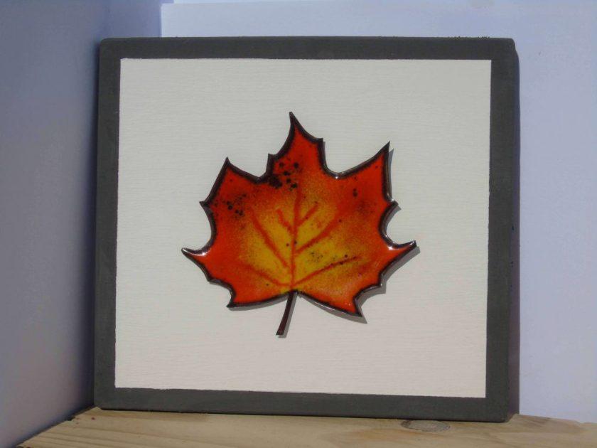 enamelled leaf on wooden board