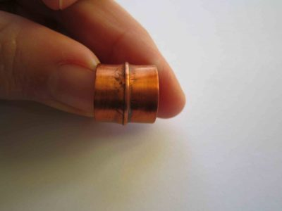 fold formed copper ring with light patina being held