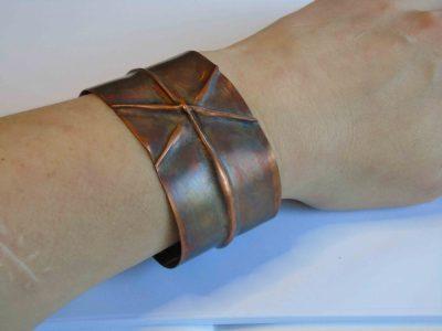 Cuff bracelet with cross pattern being worn