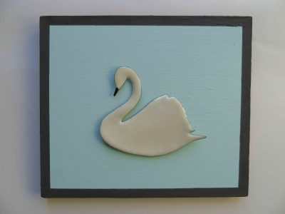 White enamelled swan with black beak on blue and grey painted wooden board