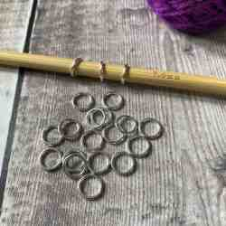 Set of silver ring stitch markers, with a knitting needle and some yarn in the background