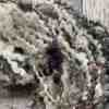 Closeup detail of textured black, white and grey art yarn on wood background