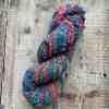 Self-striping multicolour hand spun yarn by Eleanor Shadow on a wood background. Hand spun yarn for sale