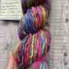 Eleanor Shadow's hand holds multicolour single ply hand spun yarn. You can see some of the label info the yarn comes with in the background.
