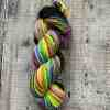 Bright neon, chain-plied hand spun yarn on a wooden background. Rainbow neon colours.