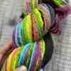 Detail of neon chain-plied hand spun yarn, held by Eleanor Shadow's hand.