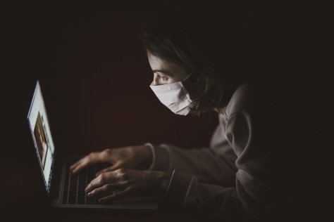 laptop user wearing a mask