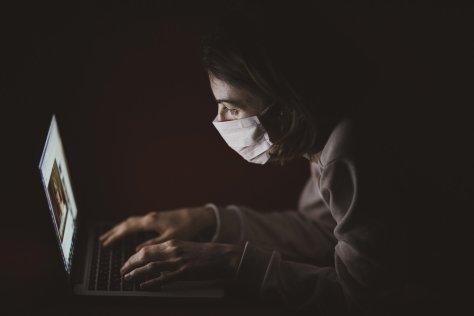 laptop user wearing a mask