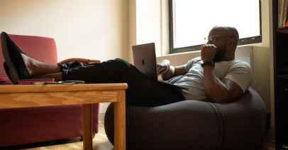 Man sitting on a beanbag using a laptop