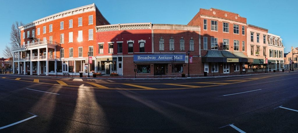 An image depicting a strip of 3 story buildings in a small town.