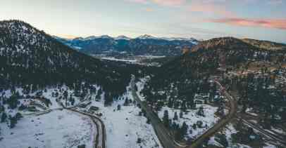 Roads winding through snowy, evergreen-covered mountains in Colorado.