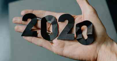 """A hand is shown, palm facing up, holding black cut out numbers that spell """"2020"""""""