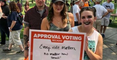 "Two women and a man hold a sign that says, ""Approval voting because: every vote matters, no matter how small!"""