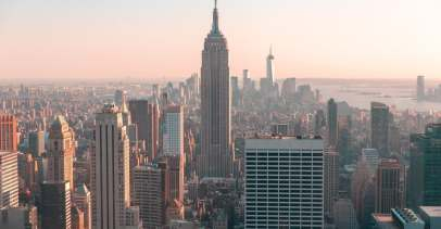 A photo of the New York City skyline as seen from midtown, with the empire state building in the middle of the photo.