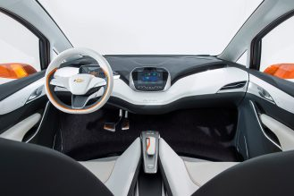 2015 Chevrolet Bolt EV Concept all electric vehicle interior. Unique crossover proportions provide a calm, welcoming interior blending technology and efficiency with a roomy, airy feel. Glass roof, thin seat design, aluminum seat structure, flow-through flat floor, anodized orange accents and 10 inch capacitive touch screen.