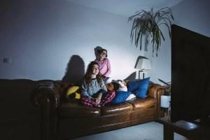 Electrodomésticos de bajo consumo eléctrico. Dos niñas de entre 10 y 12 años en un sofá con un perro, mirando televisión en penumbras.