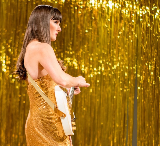 """A white woman with long brown hair and bangs wearing a gold dress and holding a guitar, surrounded by gold tinsel, part of the """"Woman in E"""" performance piece."""