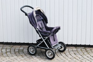 A purple baby stroller against a white wall