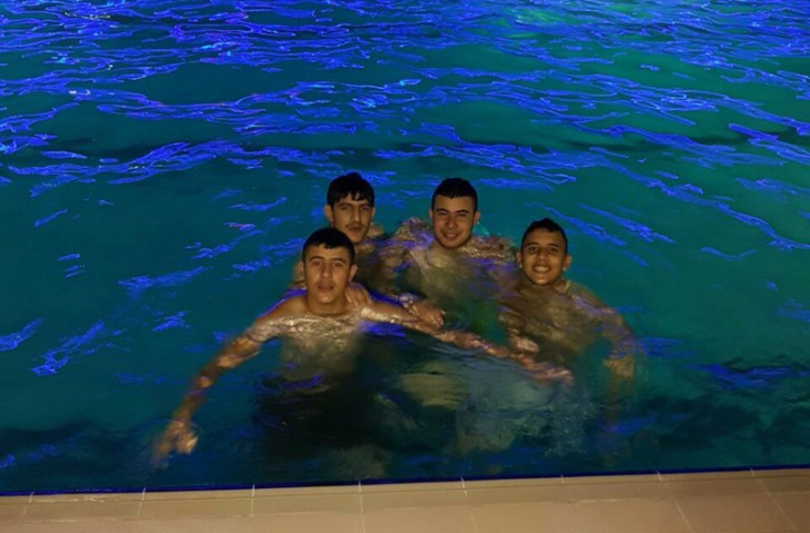 Four boys pose for camera while in a swimming pool